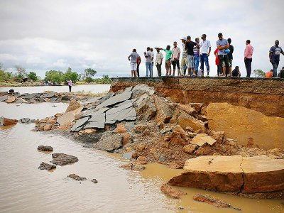 Des habitants debout près d'une route endommagée entre Beira et Chimoio, dans le centre du Mozambique, le 19 mars 2019, après le passage du cyclone Idai - ADRIEN BARBIER [AFP]
