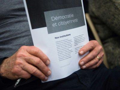 Un homme tient des documents dans le cadre du Grand débat national à Bollène (Vaucluse) le 28 février 2019 - CLEMENT MAHOUDEAU [AFP/Archives]
