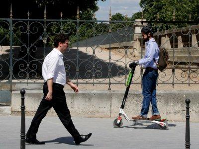 Un homme sur une trottinette électrique route sur les trottoirs, le 9 juillet 2018 à Paris - FRANCOIS GUILLOT [AFP/Archives]