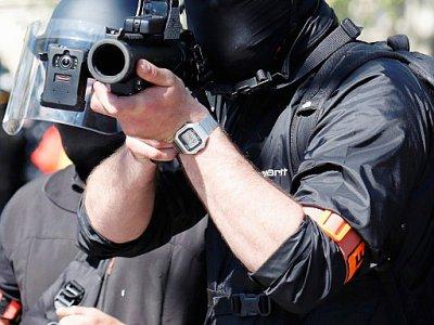 """Policier pointant un lanceur de balles de défense (LDB) vers la manifestation de """"gilets jaunes"""", à Paris, le 20 avril 2019    Zakaria ABDELKAFI [AFP/Archives]"""