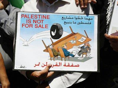 """""""La Palestine n'est pas à vendre"""", indique une affiche brandie par un manifestant à Ramallah, en Cisjordanie, le 24 juin 2019    ABBAS MOMANI [AFP]"""