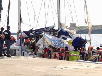 Capture d'écran depuis une vidéo de Local Team, le 6 juillet 2019, montrant des policiers italiens en faction près du navire humanitaire Alex après son arrivée dans le port de l'île de Lampedusa    - [Local Team/AFP]