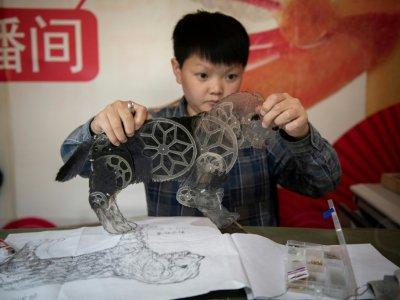 Jin Xinchun, membre d'une troupe de théâtre de marionnettistes, crée un chien, le 9 mai 2019    NICOLAS ASFOURI [AFP]