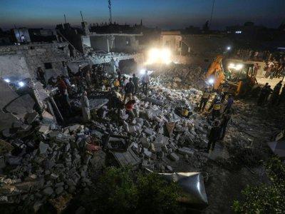 """Des membres des """"Casques blancs"""", les secouristes syriens, cherchent d'éventuels survivants dans les ruines d'un immeuble touché par une frappe du régime à Saraqeb dans la province d'Idleb (nord-ouest de la Syrie), le 22 juin 2019    Omar HAJ KADOUR [AFP/Archives]"""