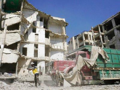 Un Casque blanc syrien devant un immeuble détruit par une frappe aérienne du régime de Damas, le 12 juillet 2019 à Idleb - Muhammad HAJ KADOUR [AFP]