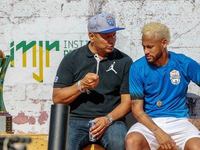 Le footballeur Neymar(d) écoute son père Neymar Senior le 13 juillet lors d'un tournoi au bénéfice de sa fondation à Praia Grande, au Brésil    Miguel SCHINCARIOL [AFP/Archives]