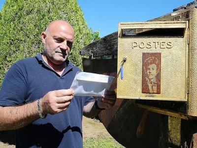 Bernard Colin, le gardien du cimetière de l'Ouest à Charleville-Mézières depuis 37 ans, sort une lettre de la boîte aux lettres dédiée au poète Arthur Rimbaud, le 21 juin 2019    FRANCOIS NASCIMBENI [AFP]