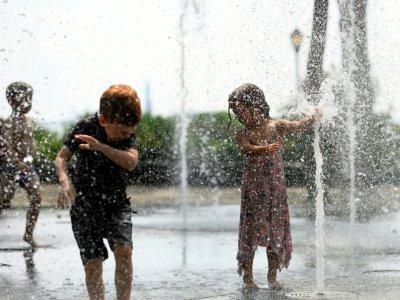 Des enfants jouent dans une fontaine publique à New York, le 19 juillet 2019    Johannes EISELE [AFP]