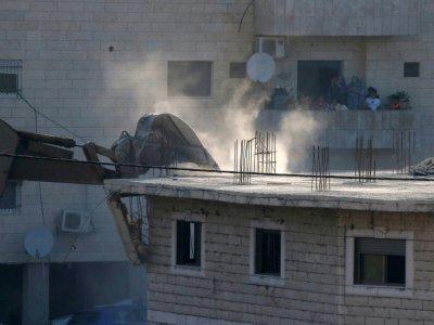 Photo prise le 22 juillet 2019 depuis la Cisjordanie occupée montrant les forces israéliennes s'apprêtant à démolir un immeuble palestinien inachevé à Wadi al-Hummus dans le secteur palestinien de Sour Baher, dans la région de Jérusalem    HAZEM BADER [AFP]