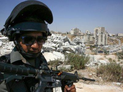 Un policier aux frontières israélien monte la garde devant des bâtiments démolis par Israël dans le quartier palestinien de Sour Baher, le 22 juillet 2019    HAZEM BADER [AFP]