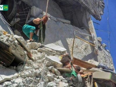 Une image prise par le site d'informations syrien SY24 le 24 juillet 2019 montre trois fillettes suspendues à plusieurs mètres du sol, après un raid aérien à Araha, dans le nord-ouest de la Syrie - Bashar al-Sheikh [SY24/AFP]