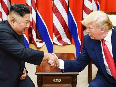 le dirigeant nord-coréen Kim Jong Un (g) et le président américain Donald Trump lors de leur rencontre sur la partie sud de la Zone démilitarisée de Panmunjon, le 30 juin 2019 - Brendan Smialowski [AFP/Archives]