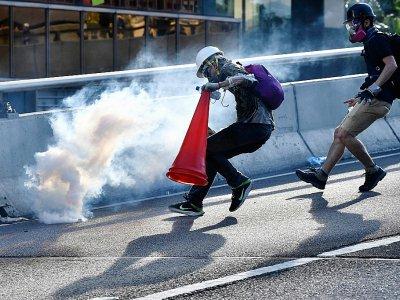Un manifestant court vers une grenade lacrymogène tirée par la police pour la recouvrir d'un cône de signalisation, le 5 août 2019 à Hong Kong    Anthony WALLACE [AFP/Archives]