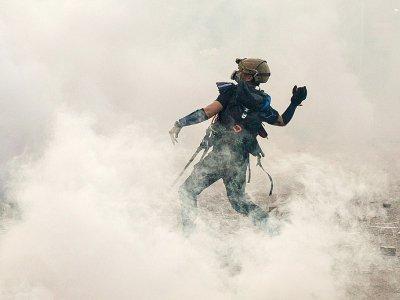 Un manifestant prodémocratie lance une brique sur les forces de l'ordre qui viennent de tirer des gaz lacrymogènes, le 5 août 2019 à Hong Kong    Isaac Lawrence [AFP/Archives]