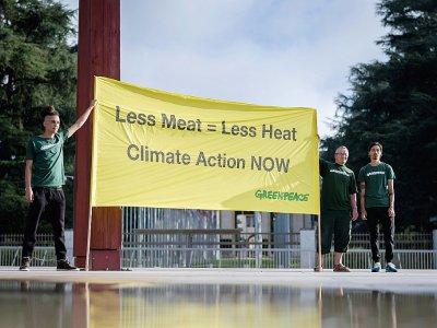 """""""Moins de viande = moins de chaleur, Action pour le climat maintenant"""" sur une banderole brandie par des militants de Greenpeace, le 8 août 2019 à Genève, avant la publication du rapport du Giec sur le climat et les terres    FABRICE COFFRINI [AFP]"""