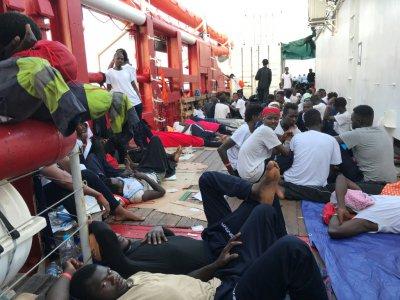 """Des migrants rescapés se reposent sur le pont du navire """"Ocean Viking"""" des ONG SOS Méditerranée et Médecins sans Frontières (MSF), durant une opération en mer Méditerranée, le 13 août 2019. - Anne CHAON [AFP]"""