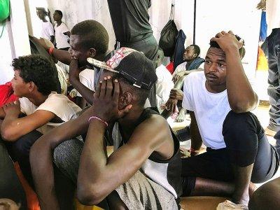 Des migrants à bord de l'Ocean Viking écoutent le coordinateur de  l'expédition, le 21 août 2019    Anne CHAON [AFP]