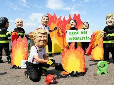 Des activistes de l'organisation Oxfam portant des masques représentant les dirigeants du G7 manifestent en marge du sommet du G7 à Biarritz, le 23 août 2019.    Bertrand GUAY [AFP]