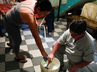 L'infirmière vénézuélienne Francis Guillen (g) prépare avec son père du gel pour cheveux chez elle, le 21 août 2019 à Caracas    Federico PARRA [AFP]