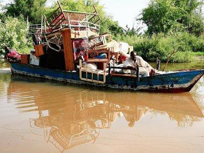 Des Soudanais transportent leurs biens sur un bateau après des inondations dans le village de Wad Ramli, sur les rives du Nil, au nord de la capitale Khartoum, le 26 août 2019 - Ebrahim HAMID [AFP]
