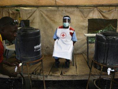 Un membre du personnel sanitaire veille à ce que les gens se lavent les mains pour lutter contre l'épidémie d'Ebola à la frontière entre la RDC et l'Ouganda, le 13 juin 2019. - ISAAC KASAMANI [AFP/Archives]