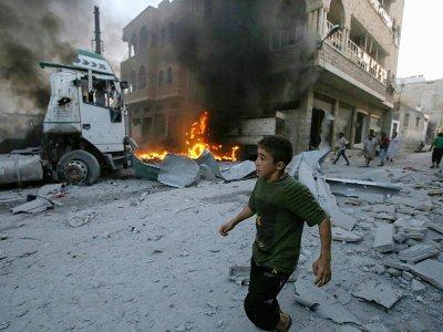 Un garçon court après qu'un  incendie s'est déclaré dans un bâtiment après un raid aérien du régime syrien contre la ville de Maaret al-Noomane dans la province d'Idleb (nord-ouest de la Syrie), le 28 août 2019    Abdulazez Ketaz [AFP]