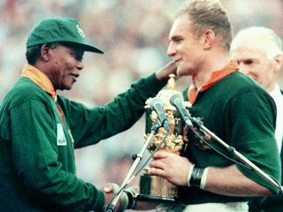 Le capitaine des Springboks François Pienaar reçoit le trophée Webb Ellis des mains du président Nelson Mandela, le 4 juin 1995 à Johannesburg - Jean-Pierre MULLER [AFP/Archives]