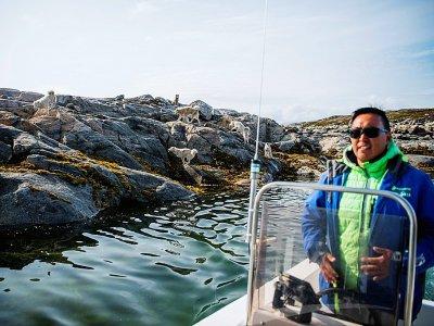 Kunuk Abelsen, 27 ans, quitte en bateau une île où se trouvent ses chiens au Groenland, le 19 août 2019    Jonathan NACKSTRAND [AFP]