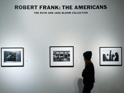 """Une visiteuse regarde des images du photographe Robert Frank tirées de son livre """"Les Américains"""", lors d'une exposition à Sotheby's à New York (Etats-Unis), le 17 décembre 2015.    Bryan Thomas [GETTY IMAGES NORTH AMERICA/AFP/Archives]"""
