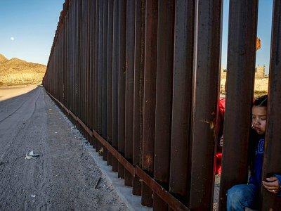 Une enfant passe la tête dans une portion de la barrière frontalière contruite entre le Mexique et les Etats-Unis, le 19 mars 2019 à Anapra (Nouveau-Mexique)    Paul Ratje [AFP/Archives]
