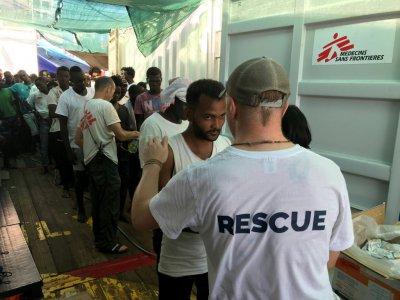 Un membre de l'équipe de sauvetage de l'Ocean Viking parle avec un migrant à bord du navire humanitaire, le 21 août 2019    Anne CHAON [AFP/Archives]