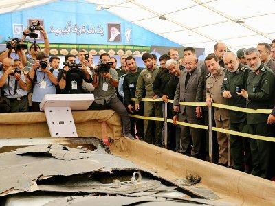 Le chef des Gardiens de la révolution iraniens, Hossein Salami (2-D) et le général Amir Ali Hajizadeh (D) regardent ce qui est présenté par l'Iran comme des débris de drones américains capturés sur son territoire, au Musée de la Défense sacrée à Téhé - ATTA KENARE [AFP]