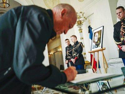 Un homme signe un registre de condoléances pour le président Jacques Chirac au Palais de l'Elysée, le 28 septembre 2019.    LUCAS BARIOULET [AFP]