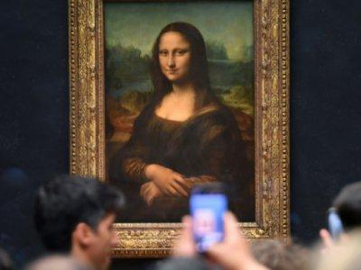 Des visiteurs prennent des photos de La Joconde, le 7 octobre 2019 à Paris - ERIC FEFERBERG [AFP]
