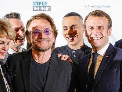 Emmanuel Macron (D), Le styliste Olivier Rousteing (2e-D) et le chanteur d'U2  Bono (G), à la conférence du Fonds mondial de lutte contre le sida, la tuberculose et le paludisme à Lyon, le 9 octobre 2019 - LUDOVIC MARIN [AFP]