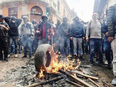 Des manifestants opposés à la hausse du prix du carburant font brûler des pneus lors d'affrontements avec la police, le 9 octobre 2019 à Quito, en Equateur - Martin BERNETTI [AFP]