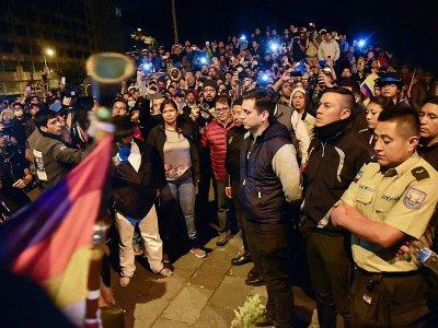 Les membres des forces de l'ordre (D), retenus par des manifestants, attendent d'être remis à des représentants des Naions unies à Quito le 10 octobre 2019 - RODRIGO BUENDIA [AFP]