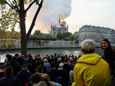 Des passants regardent les flammes dévorer la toiture de la cathédrale Notre-Dame, le 15 avril 2019 à Paris    GEOFFROY VAN DER HASSELT [AFP/Archives]