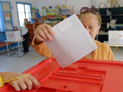 Une Tunisienne glisse son bulletin dans l'urne, lors des législatives, le 6 octobre 2019 à Tunis    FETHI BELAID [AFP]