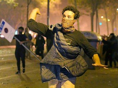 Des manifestants indépendantistes catalans lancent des projectiles sur les policiers à Barcelone le 16 octobre 2019 - LLUIS GENE [AFP]