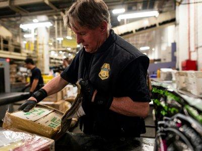 Un douanier trouve des pilules estampillées oxycodone dans des paquets au centre de tri postal de l'aéroport  John F. Kennedy, le 24 juin 2019 à New York    Johannes EISELE [AFP]