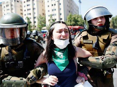 La police anti-émeutes arrête une manifestante, à Santiago le 21 octobre 2019    Pablo VERA [AFP]