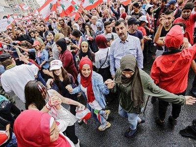 Des manifestants libanais dansent avec des drapeaux nationaux lors d'une manifestation sur la place al-Nour, à Tripoli dans le nord du pays, le 23 octobre 2019    Ibrahim CHALHOUB [AFP]
