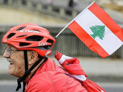 Un cycliste libanais chevauche avec un drapeau national à travers la région de Dbayeh au nord de Beyrouth, en soutien aux protestations au Liban contre l'élite dirigeante et les conditions économiques désastreuses, le 23 octobre 2019    JOSEPH EID [AFP]