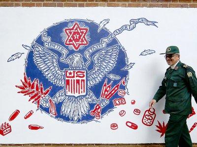 Un Gardien de la Révolution iranien passe devant une fresque murale sur l'enceinte de l'ancienne ambassade américaine à Téhéran, le 2 novembre 2019    ATTA KENARE [AFP]