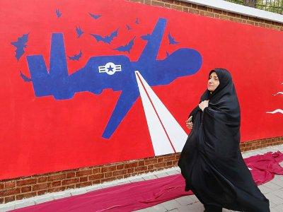 Une Iranienne passe devant une fresque murale sur l'enceinte de l'ancienne ambassade américaine à Téhéran, le 2 novembre 2019    ATTA KENARE [AFP]
