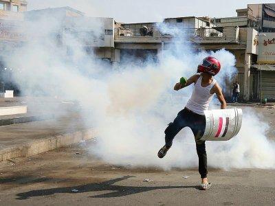 Casque de moto sur la tête, un Irakien court pour échapper aux gaz lacrymogènes, lors d'une manifestation contre le pouvoir, à Bagdad le 7 novembre 2019 - AHMAD AL-RUBAYE [AFP]