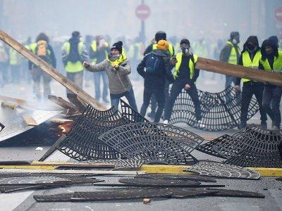 """Des manifestants """"gilets jaunes"""" utilisent les grilles entourant le pied des arbres pour bloquer une rue, le 1er décembre 2019 à Paris    Alain JOCARD [AFP]"""