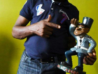 L'acteur ivoirien Michel Gohou pose avec une statue du gendarme de Abobo, à Abidjan le 20 novembre 2019.    SIA KAMBOU [AFP]
