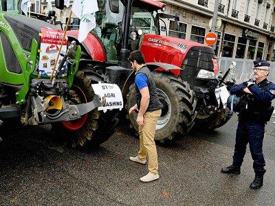 Un policier est positionné près de tracteurs lors d'une manifestation d'agriculteurs le 22 octobre 2019 à Lyon - JEAN-PHILIPPE KSIAZEK [AFP/Archives]